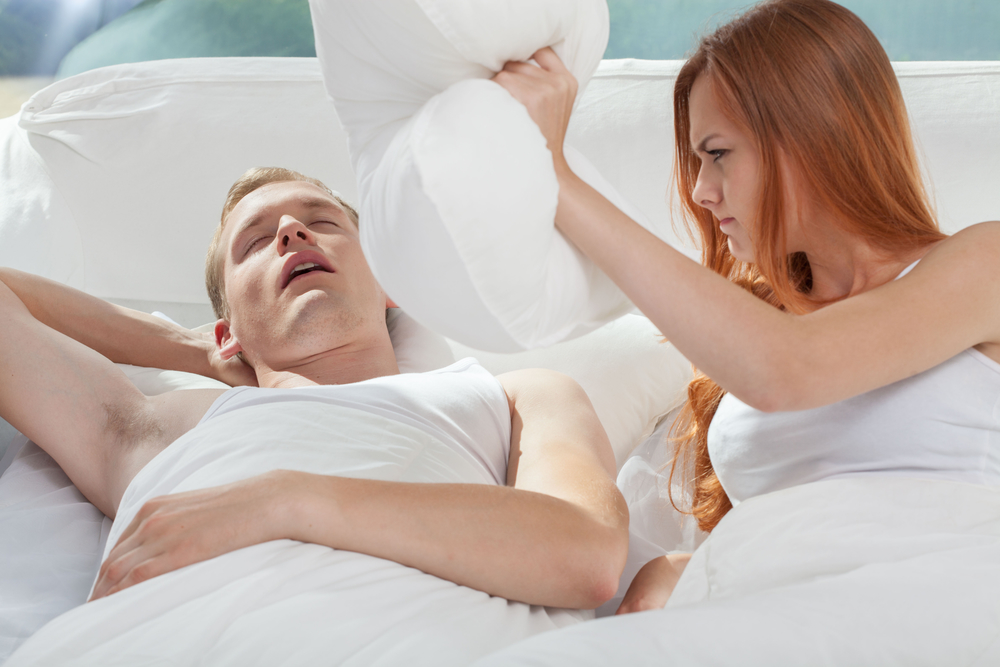 Woman about to hit husband with pillow because of his snoring